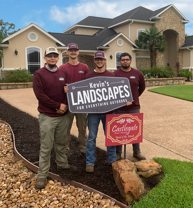 Three team members in front of a house holding the company logo